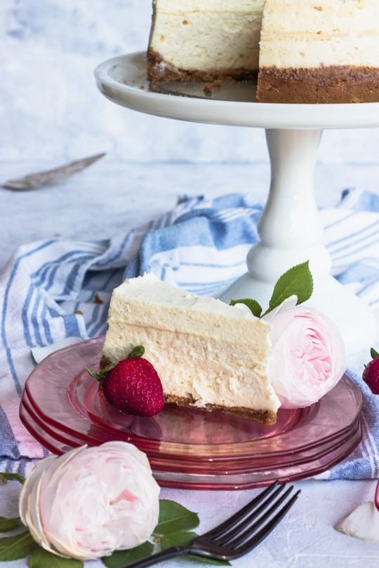 Slice of Vanilla Bean Cheesecake with Strawberry and Pink Rose Garnish