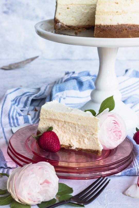 Slice of Vanilla Bean Cheesecake with Strawberry and Pink Rose Garnish