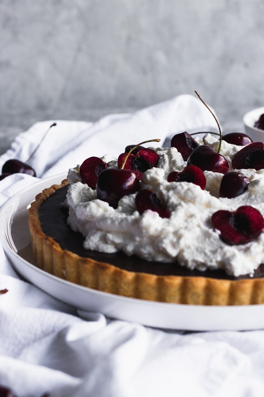 Chocolate Cherry Tart -- A delicate pastry case filled with a layer of sweet cherries and topped with chocolate ganache. Pile it high with whipped cream and top with more cherries. || Good Things Baking Co. #goodthingsbaking #chocolatecherry #darkchocolate #chocolateganache #chocolatetart #tartrecipe