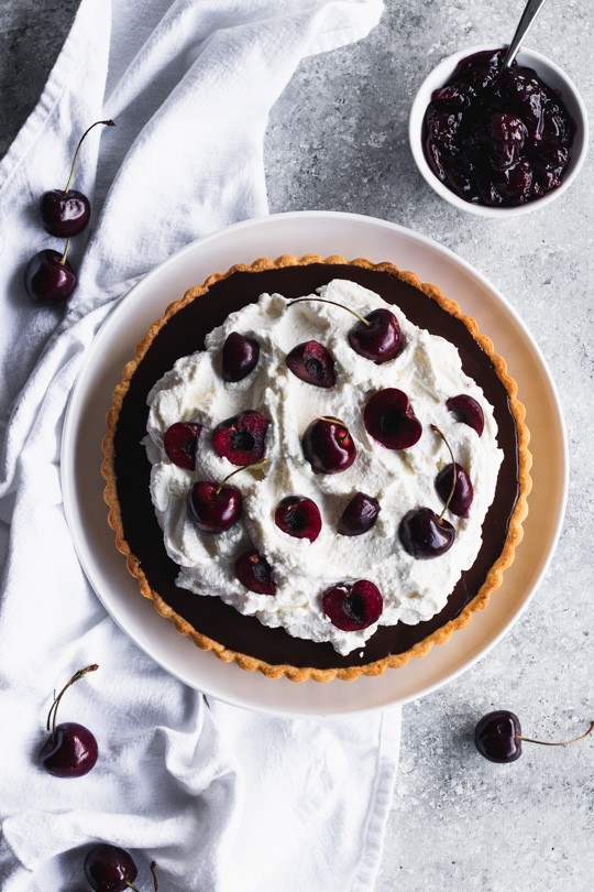 Chocolate Cherry Tart -- A delicate pastry case filled with a layer of sweet cherries and topped with chocolate ganache. Pile it high with whipped cream and top with more cherries.