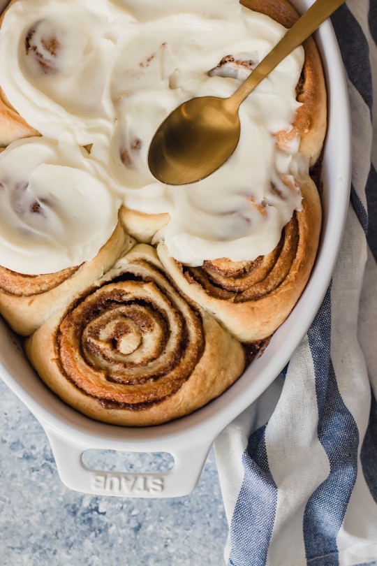 A pan of perfectly swirled cinnamon rolls with fluffy white frosting being spread over them.