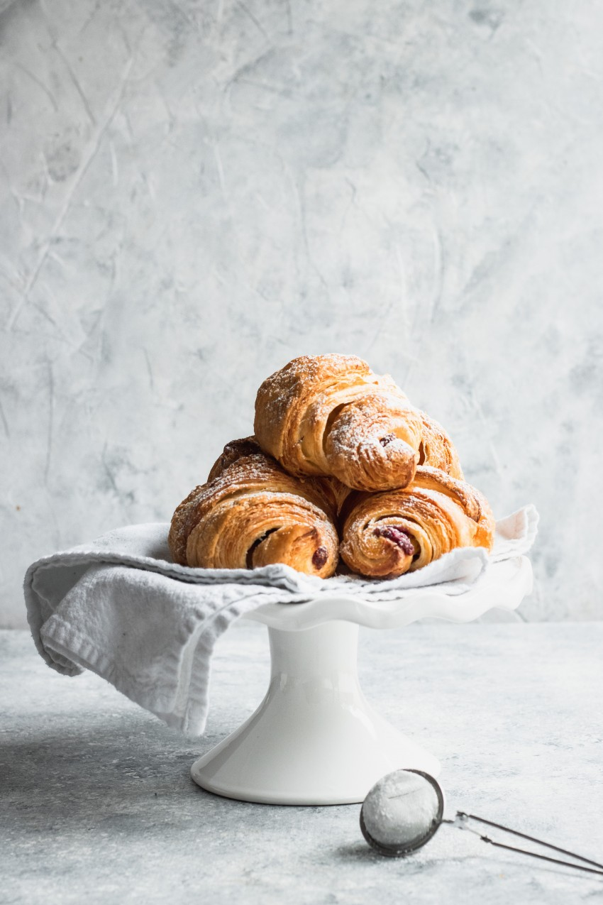 Piled on a white plate, these flaky croissants are filled with Chocolate and Raspberry Filling and dusted with powdered sugar.
