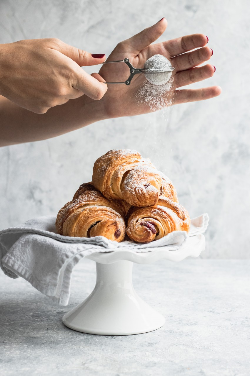 Piled on a white plate, these flaky croissants are filled with Chocolate and Raspberry Filling and being dusted with powdered sugar.