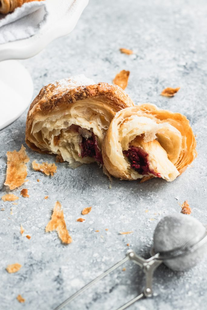 A flaky croissant torn in half to show the raspberry and chocolate filling.