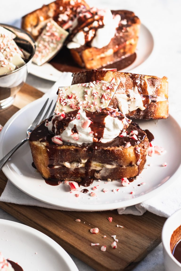 Peppermint Bark French Toast is stuffed with a cream cheese filling, then piled high with whipped cream, peppermint bark, and drizzled with chocolate ganache