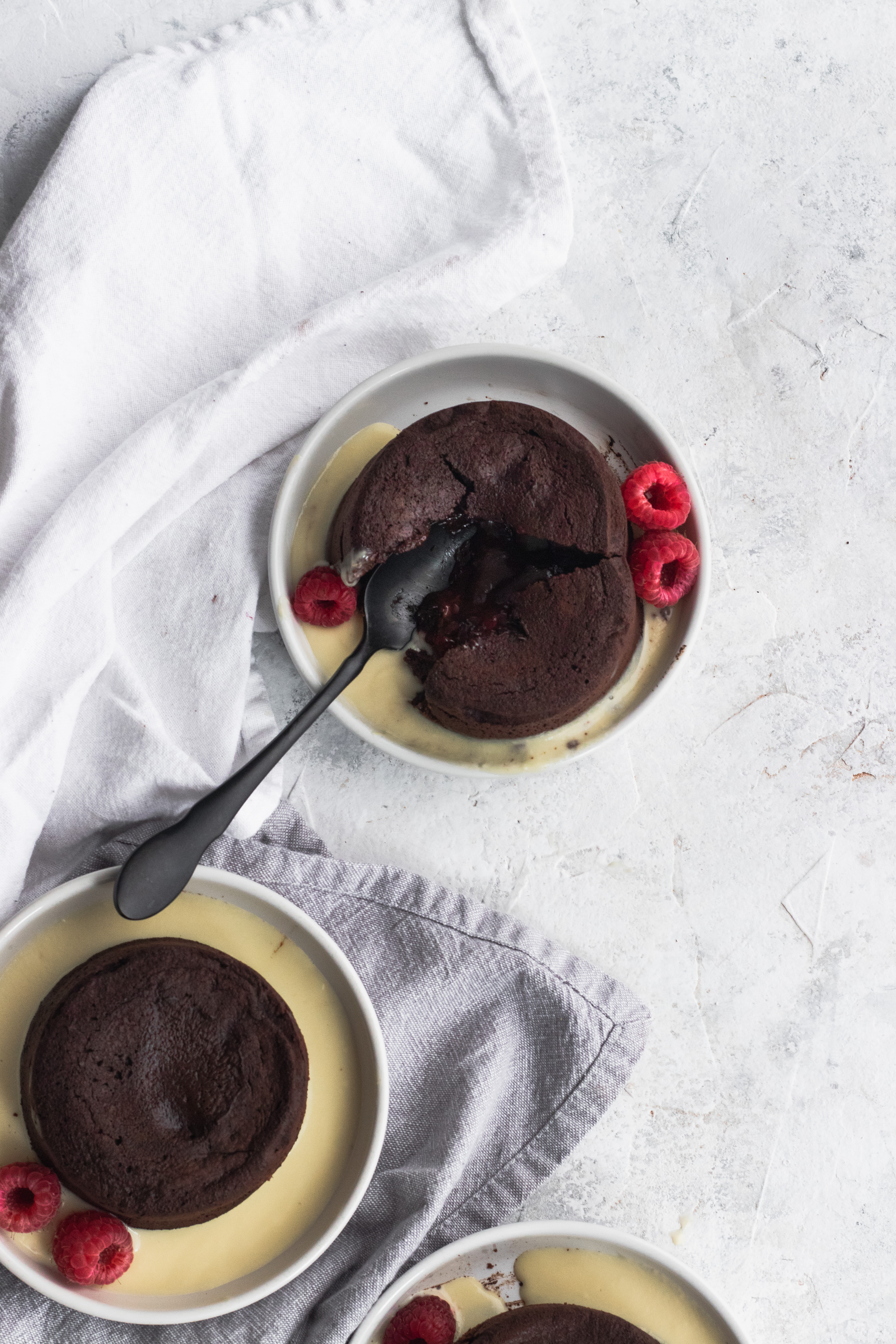 Raspberry Chocolate Lava Cakes with an oozing chocolate and raspberry center, garnished with creme anglaise and fresh raspberries