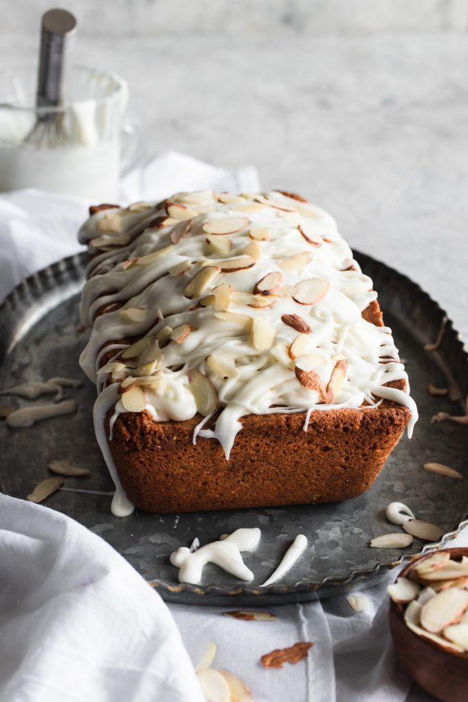 A loaf of Glazed Almond Poppy Seed Bread topped with sliced almonds