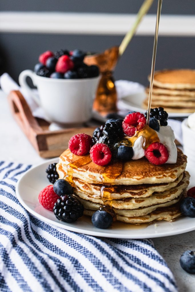 A stack of overnight sourdough pancakes, topped with whipping cream and berries, then with a drizzle of maple syrup.