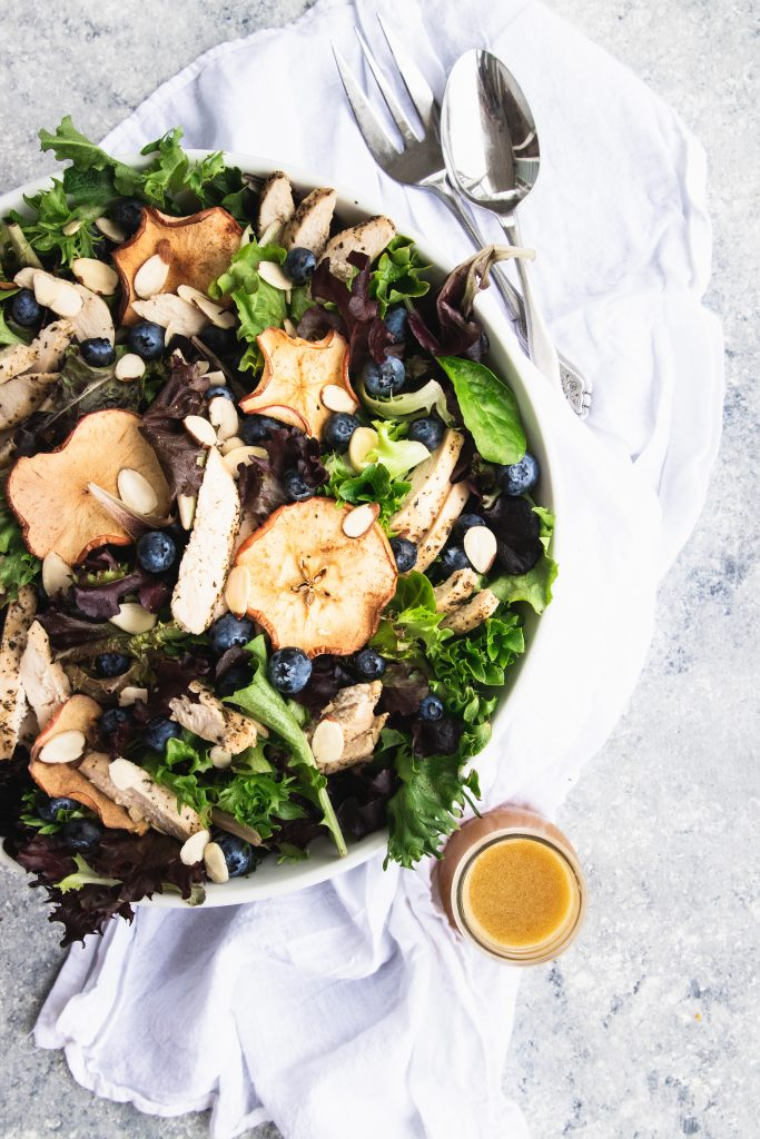 A giant bowl of fresh spring greens topped with dried apple chips, fresh blueberries, and slices of chicken. A small jar of fuji apple dressing is waiting to be pour over the salad.