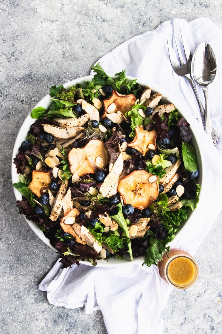 A giant bowl of fresh spring greens topped with dried apple chips, fresh blueberries, and slices of chicken. A small jar of fuji apple dressing is waiting to be poured over the salad.