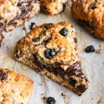 A close up of a scone filled with chunks of chocolate and blueberries