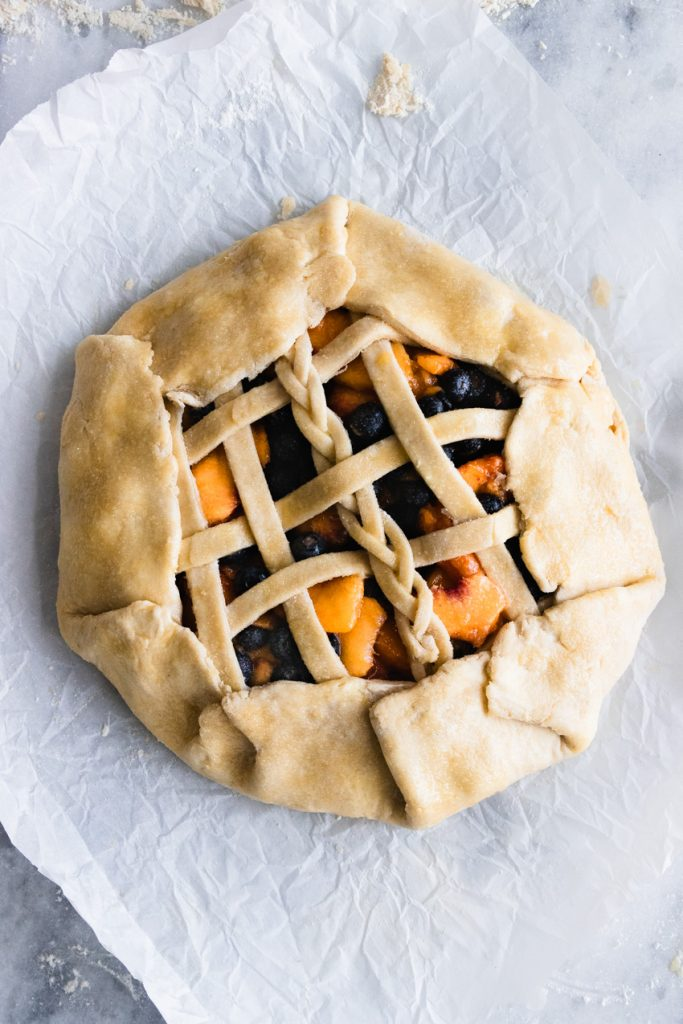 An uncooked Blueberry Peach Galette