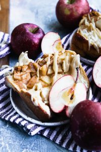 A slice of apple bread, full of soft, spiced apples and drizzled with brown sugar glaze