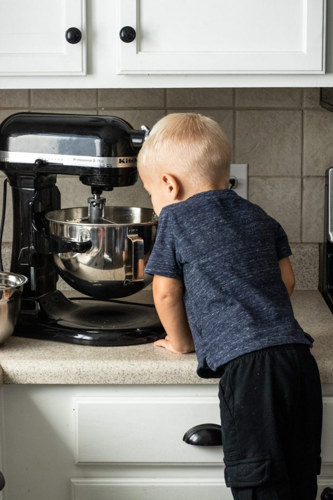 Picture of a little boy peering into a mixing bowl