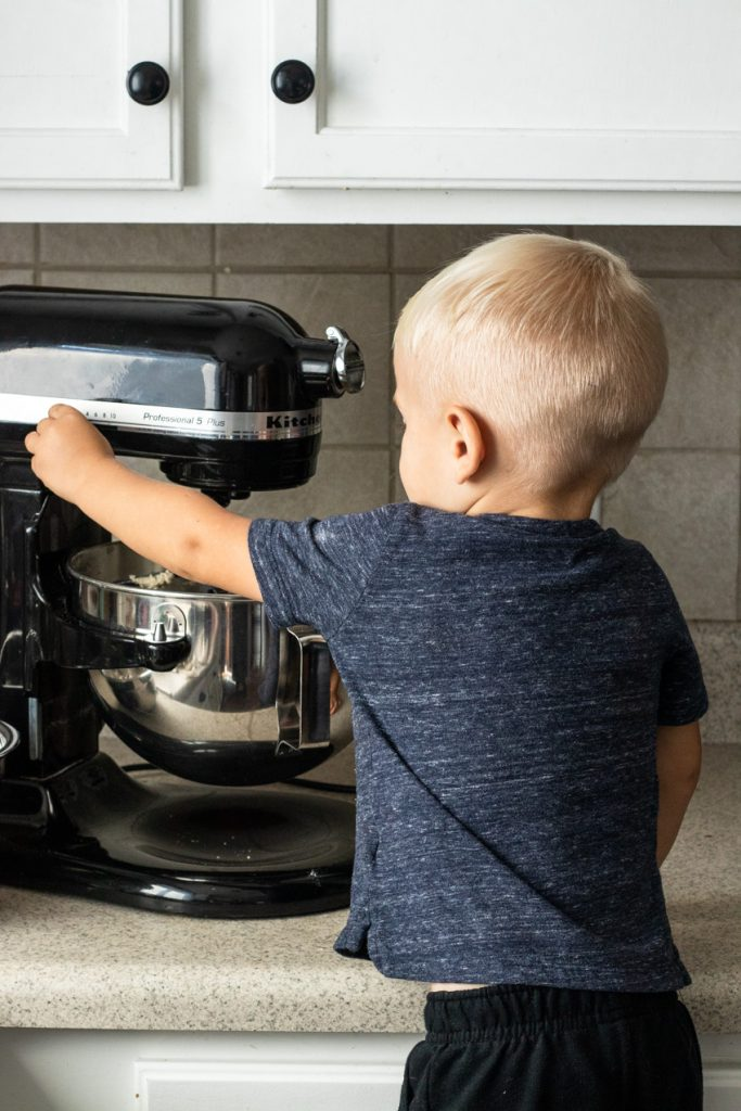 A little boy turning the mixer off--letting kids turn on switches is a great tip for baking with kids!