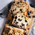 A sliced loaf of blueberry muffin bread with crumb topping