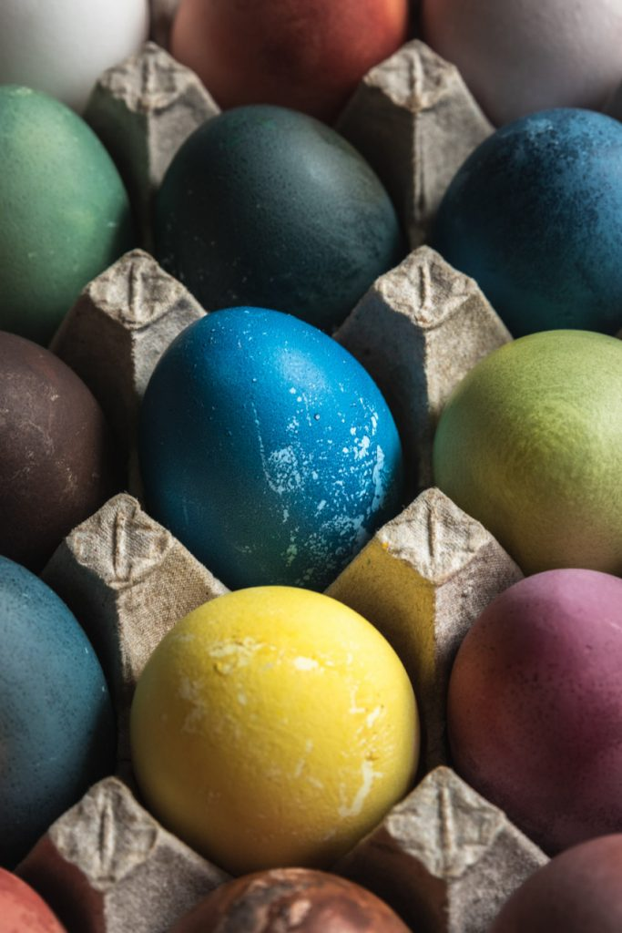 A picture of easter eggs-green, yellow, blue, purple, orange, and brown--all dyed with food and food scraps.