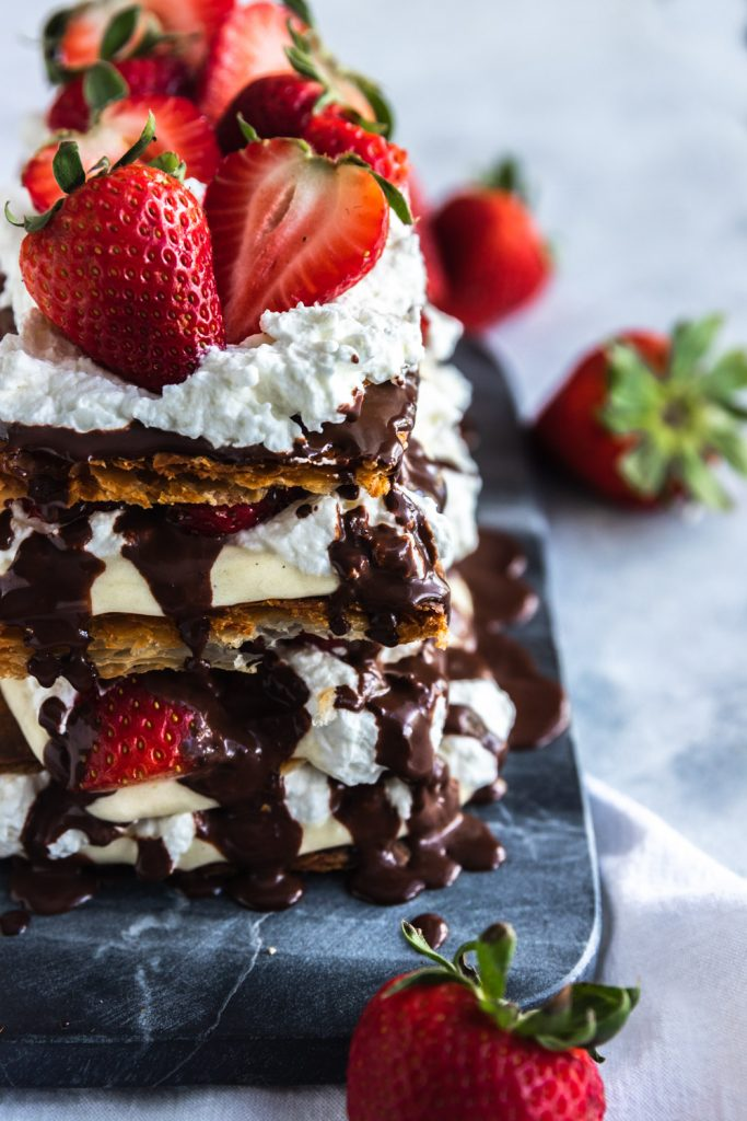 A strawberry napoleon dessert with layers of puff pastry, pastry cream, whipping cream, fresh strawberries, and chocolate ganache.