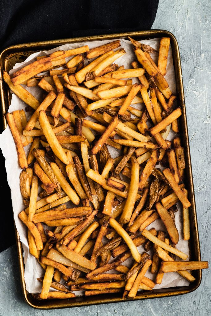 A tray of freshly fried homemade French fries, sprinkled with coarse sea salt.