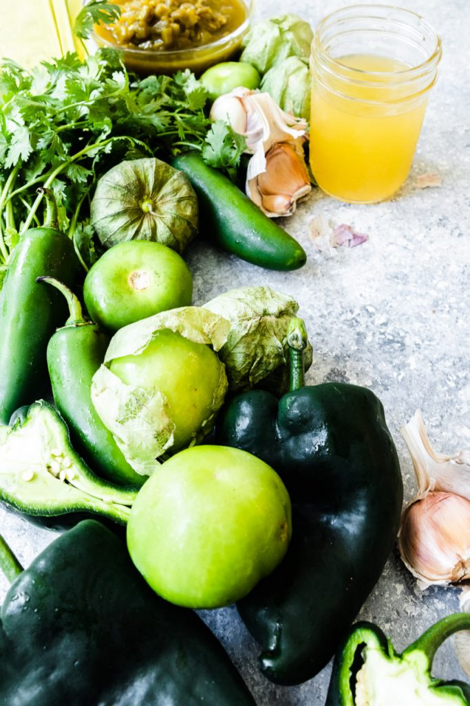 The ingredients needed for green enchilada sauce--poblano peppers, jalapenos, tomatillos, garlic, cilantro, canned green chilis, salt, broth, sea salt, and olive oil.