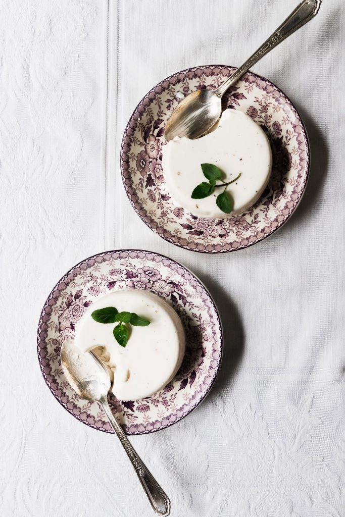 Two panna cottas on dessert plates, being shared.