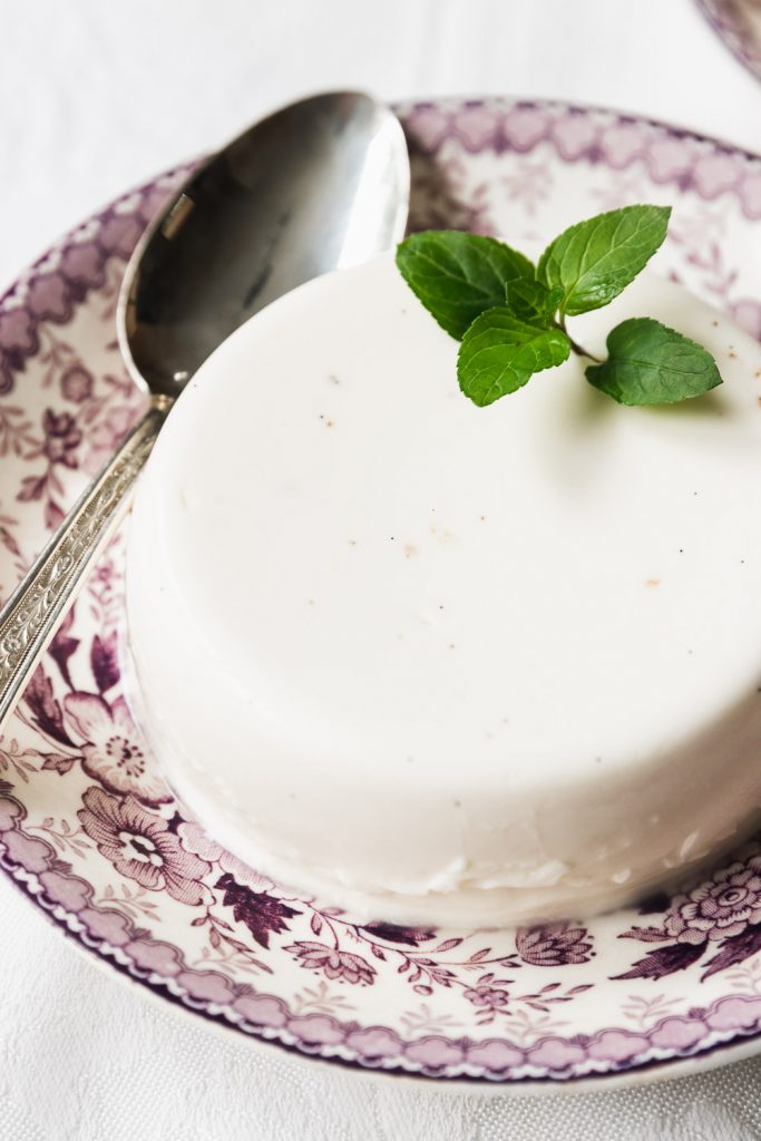 A close-up of a panna cotta garnised with a sprig of fresh mint.